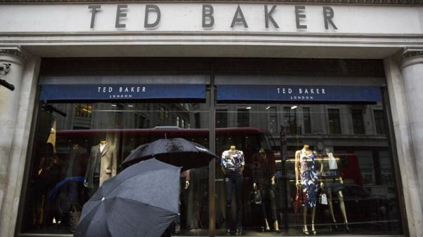 FILE PHOTO - People shelter under umbrellas as they pass a Ted Baker a store in London, Britain October 06, 2015.  REUTERS/Neil Hall