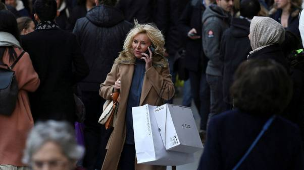 FILE PHOTO: A shopper speaks on her mobile phone as she walks along Oxford Street in London, Britain December 3, 2016. REUTERS/Neil Hall/File Photo