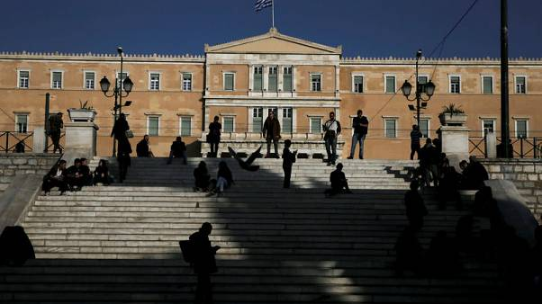 FILE PHOTO: People make their way on main Syntagma square as the parliament building is seen in the background, in Athens, Greece February 28, 2017. REUTERS/Alkis Konstantinidis/File photo