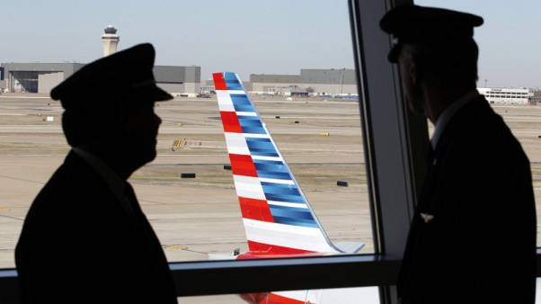 FILE PHOTO: Pilots talk as they look at the tail of an American Airlines aircraft at Dallas-Ft Worth International Airport February 14, 2013.    REUTERS/Mike Stone