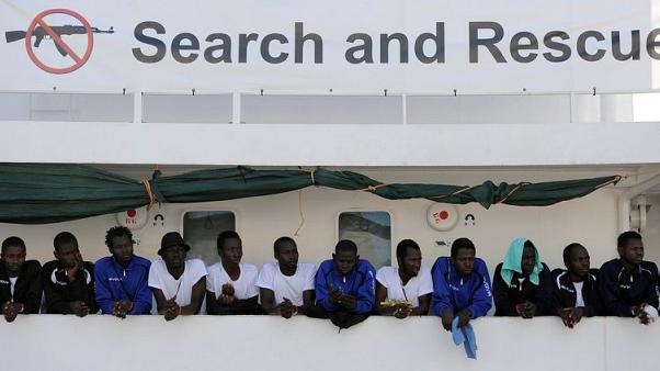 FILE PHOTO: Migrants wait to disembark from the Aquarius ship in the Sicilian harbour of Palermo, Italy October 13, 2017. REUTERS/Guglielmo Mangiapane - File Photo
