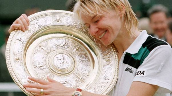 FILE PHOTO - Jana Novotna of the Czech Republic hugs the winner's trophy after victory over Nathalie Tauziat of France in the Women's Singles final at the Wimbledon Tennis Championships July 4. Novotna won the match 6-4 7-6 (7-2)/File Photo