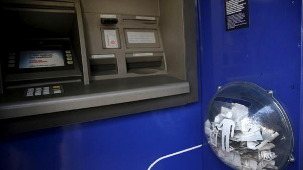 FILE PHOTO: Paper receipts from withdrawals are seen in a litter box at an Eurobank ATM that was emptied by people withdrawing cash, in Athens, Greece, June 27, 2015. REUTERS/Yannis Behrakis/File Photo