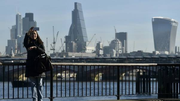 A woman takes a selfie in front of the skyline of the financial district in London, Britain February 16, 2016.  REUTERS/Hannah McKay