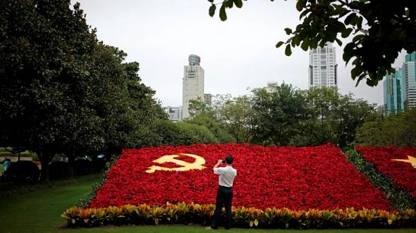 FILE PHOTO - A man takes photos of a party flag of Communist Party of China made with flowers, which promotes the 19th National Congress of the Communist Party of China (CPC), in Shanghai, China September 30, 2017. REUTERS/Aly Song