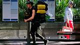 FILE PHOTO - A pedestrian walks near a foreign backpacker as he carries his belongings past a bus stop in central Sydney, Australia, May 17, 2016.  REUTERS/David Gray