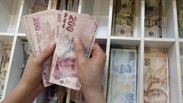رجل يعد عملات ورقية فئة 200 ليرة في مكتب صرافة في اسطنبول. أرشيف رويترز