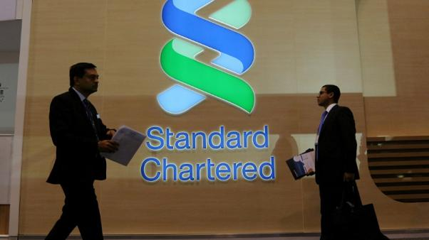 FILE PHOTO: People pass by the logo of Standard Chartered plc at the SIBOS banking and financial conference in Toronto, Ontario, Canada October 19, 2017. REUTERS/Chris Helgren/File Photo