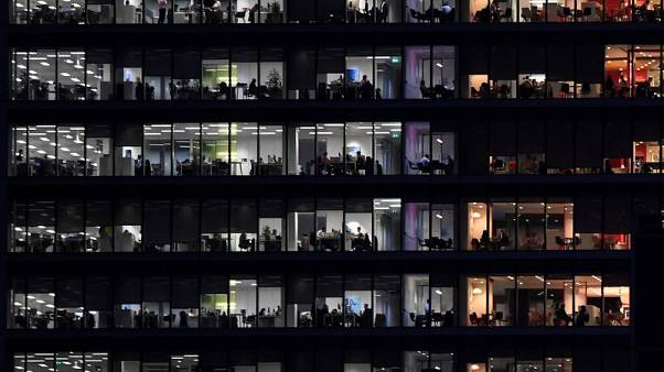 Workers are seen in an office tower in the Canary Wharf financial district at dusk in London, Britain, November 17, 2017. REUTERS/Toby Melville