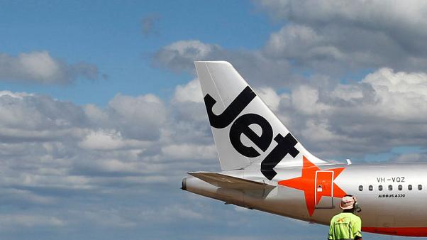 FILE PHOTO: An airport worker stands in front of a Jetstar passenger plane at Avalon Airport in Melbourne in this March 19, 2010 file photo.      REUTERS/Mick Tsikas/File Photo