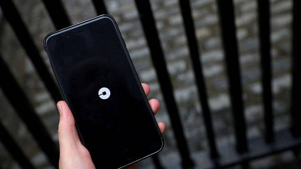 FILE PHOTO: The Uber logo is seen on mobile telephone in London, Britain, September 25, 2017. REUTERS/Hannah McKay/File Photo