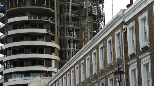 An apartment block is constructed behind a row of traditional properties in central London December 11, 2014.  REUTERS/Luke MacGregor/Files