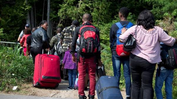 A group that stated they were from Haiti line up to cross the U.S.-Canada border into Hemmingford, Quebec, Canada, from Champlain in New York, U.S.A. August 21, 2017. REUTERS/Christinne Muschi