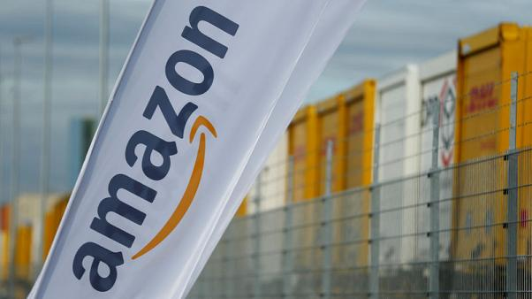 FILE PHOTO - Flags with the logo of Amazon and trailers of German postal and logistic Deutsche Post DHL Group are pictured outside the new Amazon logistic center in Dortmund, Germany November 14, 2017. REUTERS/Thilo Schmuelgen