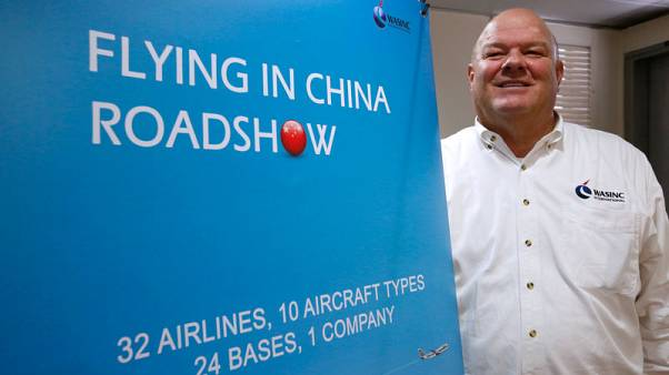 Dave Ross, President and CEO of WASINC International, poses beside a recruitment banner in Hong Kong, China November 20, 2017. Picture taken November 20, 2017.      REUTERS/Bobby Yip