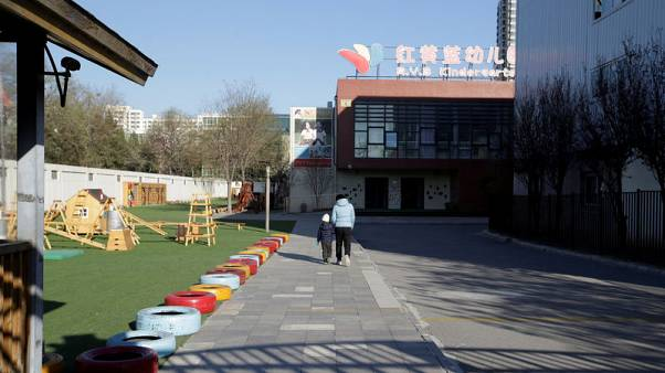 FILE PHOTO: A child walks with a parent at the kindergarten run by pre-school operator RYB Education Inc being investigated by China's police, in Beijing, China November 24, 2017. REUTERS/Jason Lee
