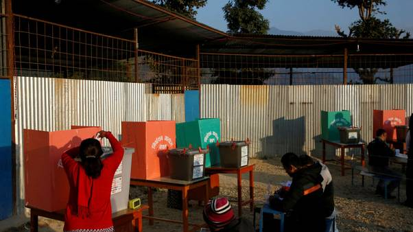 A woman (L) casts her vote in a ballot box during the parliamentary and provincial elections at Chautara in Sindhupalchok District November 26, 2017. REUTERS/Navesh Chitrakar