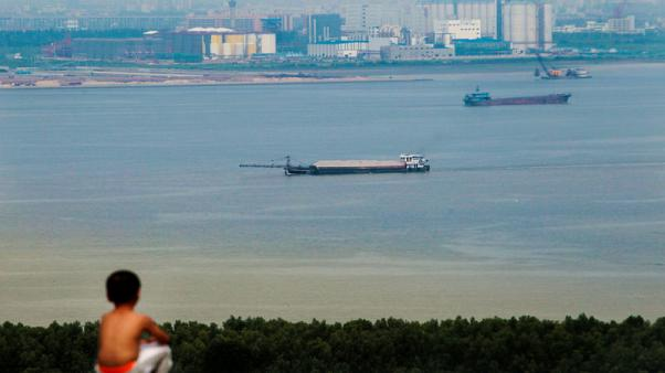 FILE PHOTO - A boy looks at cargo ships passing along the Pearl River in Guangzhou, Guangdong province, August 6, 2014.     REUTERS/Alex Lee/File Photo