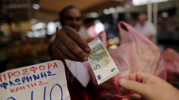 A vendor gives a five Euro bank note back to a customer at the central market in Athens, Greece, July 8, 2015. REUTERS/Christian Hartmann