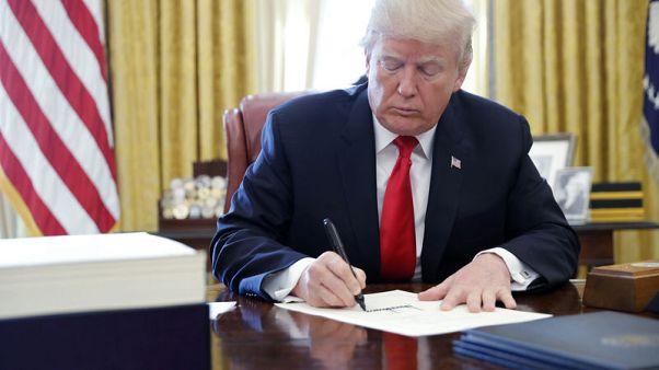 ترامب يوقع مشروع قانون الضرائب ومشروع قانون لتمويل الحكومة