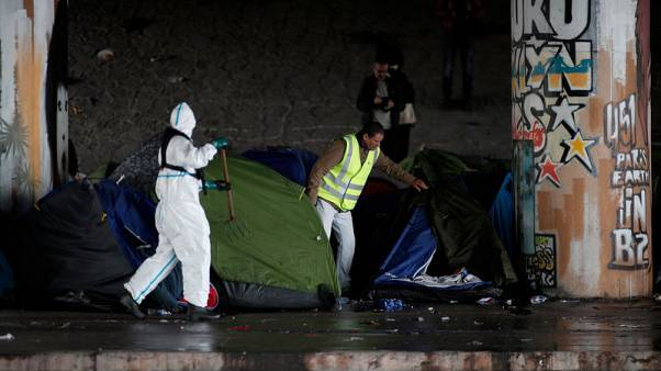 Police clear out two more migrant camps in Paris