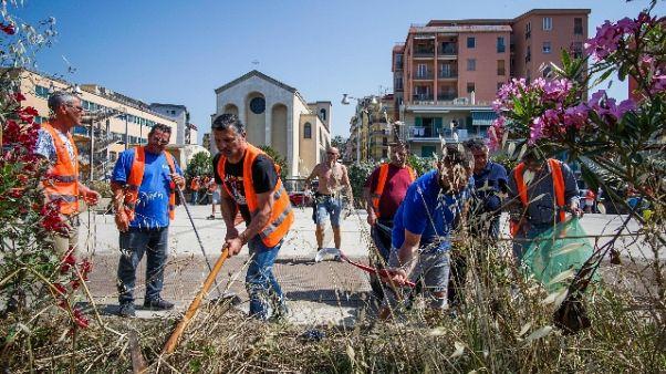 Precari ripuliscono una piazza a Bagnoli