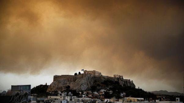 يونانيون يفرون من حريق غابات يستعر إلى الغرب من أثينا