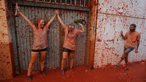 People in red - thousands hurl tomatoes in Spanish food fight