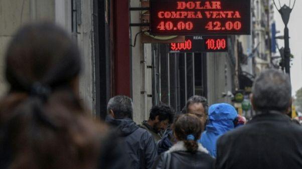Des gens passent devant un bureau de change à Buenos Aires le 30 août 2018