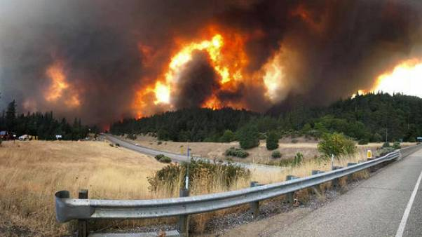 Northern California wildfire threatens homes, closes major highway