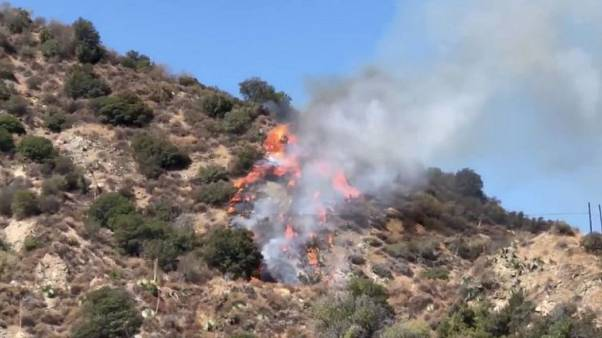 Major California highway reopens but wildfire burns on