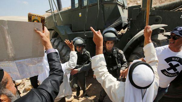 سكان الخان الأحمر يحاولون منع جرافة إسرائيلية من إغلاق الطرق المحيطة