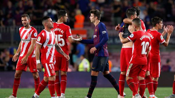 Pique rescues 10-man Barca to draw with Girona