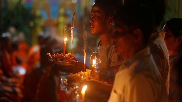 ترانيم بوذية ورش الأرز على الأرض في مهرجان الموتى بكمبوديا