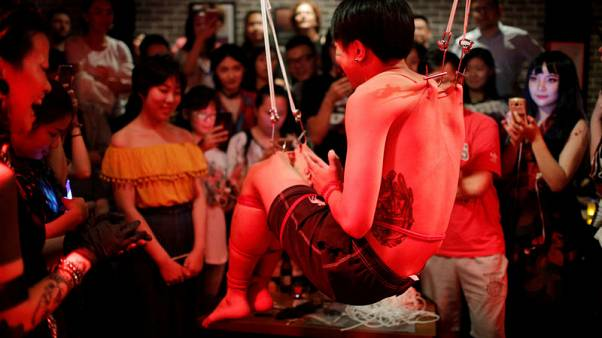 Hooked on body suspension: extreme art finds niche in China