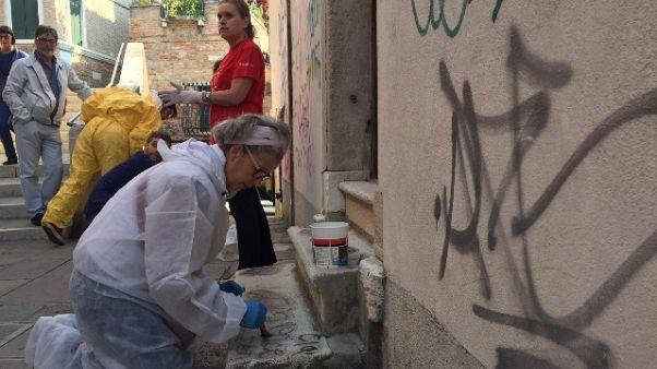 Veneziani puliscono pietre da graffiti