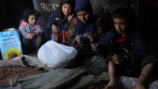Des déplacés syriens réparent leurs tentes après une tempête de pluie