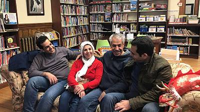 Separated by travel ban, Iranian families reunite at border library