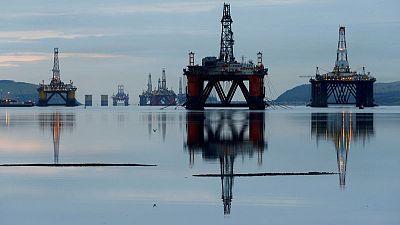 Oil prices inch down as U.S. crude stocks climb