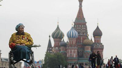 Putin, battling ratings slump, reviews Red Square military parade