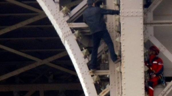 Rescuers try to talk down Eiffel Tower climber