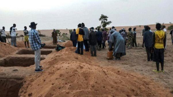 Des responsables et des habitants le 11 juin 2019 près de tombes fraichement creusées à Sobame Da, au Mali, où un massacre a fait une centaine de morts