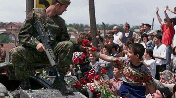 Un enfant albanais offre des roses à un soldat britannique membre des forces de l'OTAN qui se déploient à Pristina, au Kosovo, le 13 juin 1999