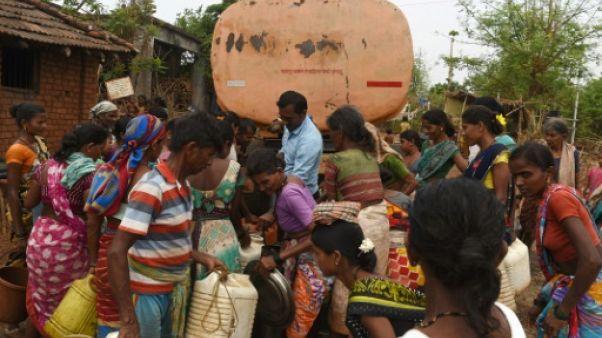 Des villageois remplissent des bidons d'eau livrée par camion citerne, dans le village indien de Shakar Pada, le 10 juin 2019