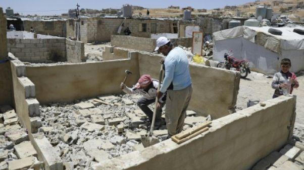Des réfugiés syriens détruisent des abris construits en béton, dans un camp à Arsal, dans le nord-est du Liban, le 10 juin 2019