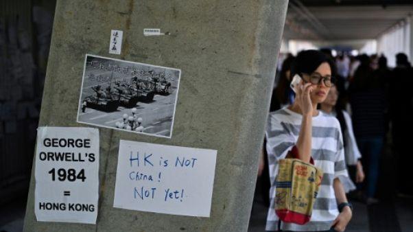 Des affichettes dénonçant le projet de loi visant à autoriser les extraditions vers la Chine sont collées sur un mur près du Conseil législatif à Hong Kong, le 14 juin 2019