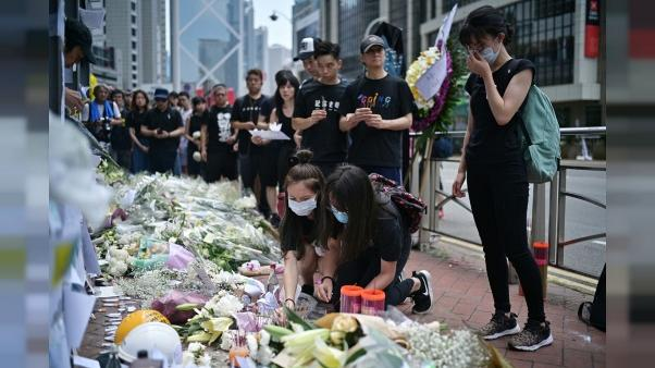 Fleurs et prières devant le lieu où est mort un opposant au projet de loi controversé autorisant les extraditions vers la Chine, à Hong Kong le 16 juin 2019