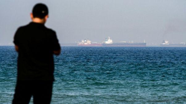 Une photo prise le 15 juin 2019 montre un homme avec au loin un pétrolier dans les eaux du Golfe au large des Emirats arabes unis