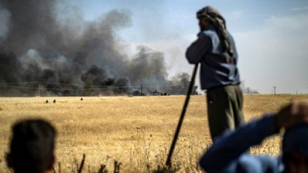 Des hommes devant un champ de blé en feu dans la province de Hassaké en Syrie, le 11 juin 2019