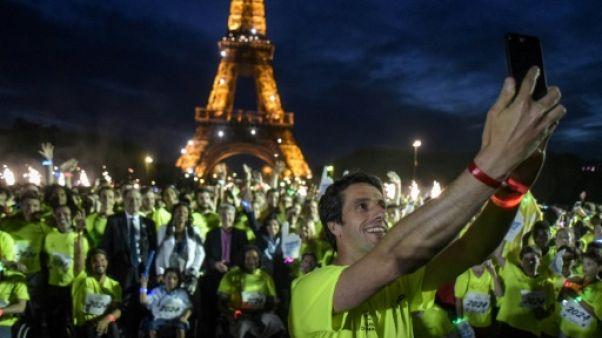 Le patron du Comité d'organisation de Paris-2024 Tony Estanguet prend un selfie avec les participants à la Journée olympique, le 23 juin 2018 à Paris